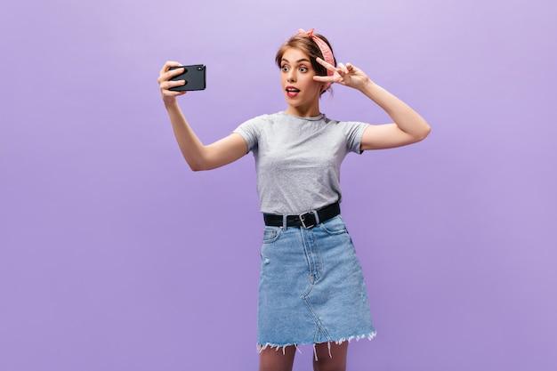 Erstaunte frau im grauen hemd zeigt friedenszeichen und nimmt selfie. charmantes mädchen im rosa stirnband mit den roten lippen, die auf lokalisiertem hintergrund aufwerfen.