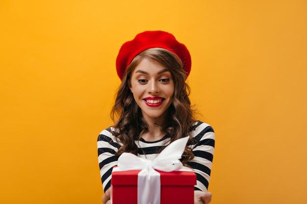 Erstaunte frau in der roten baskenmütze und im gestreiften hemd hält geschenkbox. charmante dame mit gewellter frisur im hellen hut und in der modernen bluse, die aufwirft.