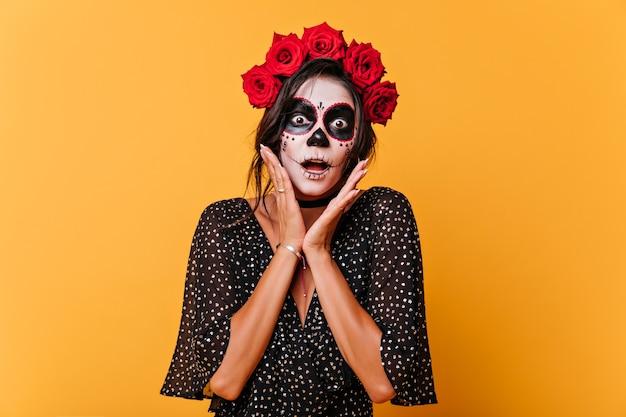 Erstaunte frau mit roten rosen im haar, die halloween feiern. beängstigendes mädchen mit muertos make-up, das auf gelbem hintergrund aufwirft.