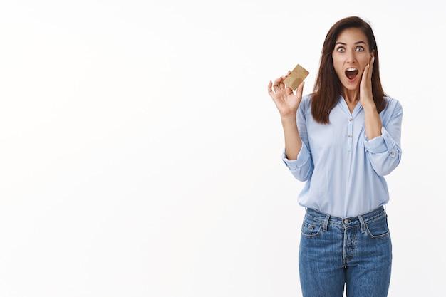 Erstaunte frau mittleren alters beeindruckte, wie schnell eine neue kreditkarte erhalten wurde, überraschte wange, überraschte, überraschte große, vernünftige cashback-zufriedenheit des online-banking-systems, stand weiße wand