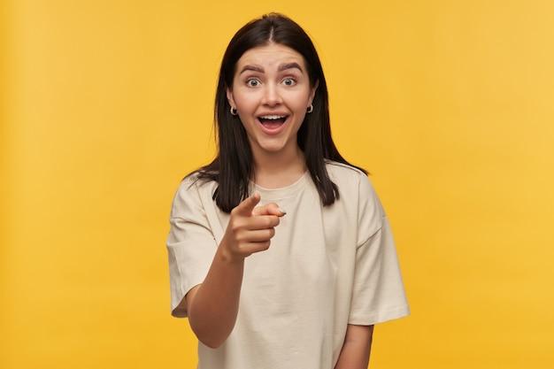 Erstaunte fröhliche junge frau mit dunklem haar und offenem mund im weißen t-shirt sieht überrascht aus und zeigt auf sie über gelbe wand yellow