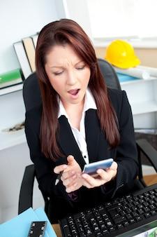 Erstaunte geschäftsfrau, die ihren taschenrechner betrachtet