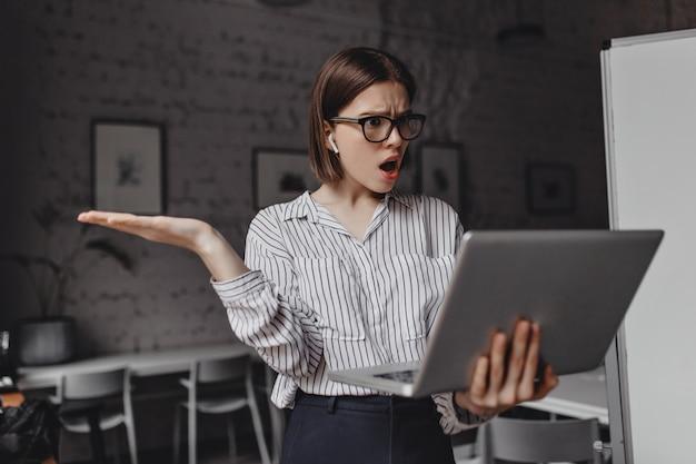 Erstaunte geschäftsfrau in brille und kopfhörern, die einen offenen laptop hält und empört über video in ihrem büro spricht.