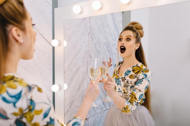 Erstaunte glückliche junge frau mit stilvoller frisur im spiegel im friseursalon
