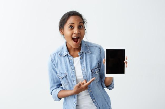 Erstaunte junge afroamerikanische junge frau, die blaues hemd über weißem t-shirt hält tablette in ihren händen hält, zeigt, wie cool diese tablette ist, mund weit offen hält, überrascht aussieht.