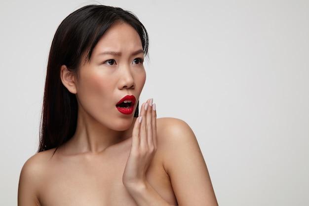 Erstaunte junge attraktive dunkelhaarige dame mit festlichem make-up, die hand zu ihrem mund hebend, während sie überraschend beiseite schaut und gegen weiße wand steht