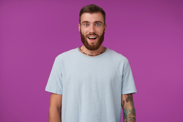 Erstaunte junge bärtige brünette mit trendigem haarschnitt in blauem t-shirt, mit großen augen und geöffnetem mund, die mit den händen nach unten auf lila posiert