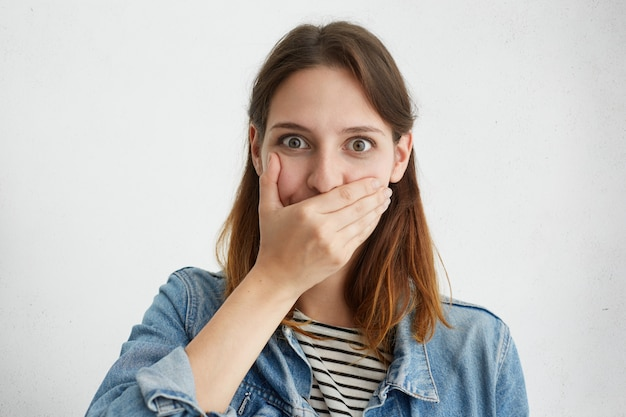 Erstaunte junge frau, die den mund mit der hand bedeckt, ihre augen voller überraschung und schock, als sie sich bemüht, die zunge zu halten und keine schockierenden gerüchte und klatsch zu verbreiten