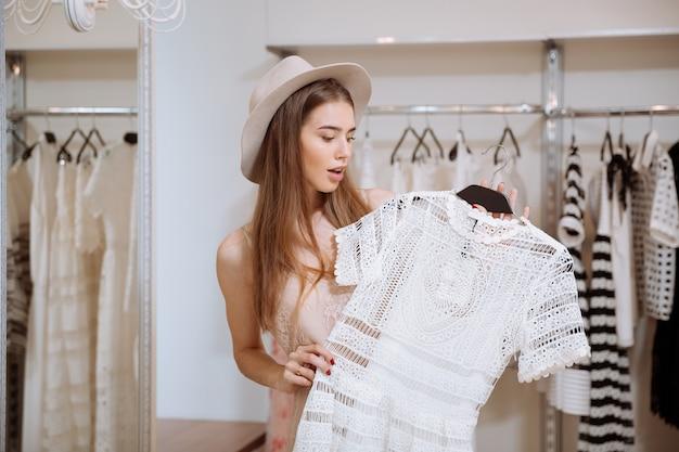 Erstaunte junge frau im hut, die weiße dres im kleidergeschäft hält und wählt