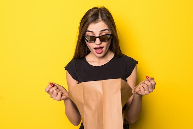 Erstaunte junge frau mit einkaufstüten. rothaariges mädchen überrascht, in einer einkaufstasche schauend, auf einer gelben wand stehend.