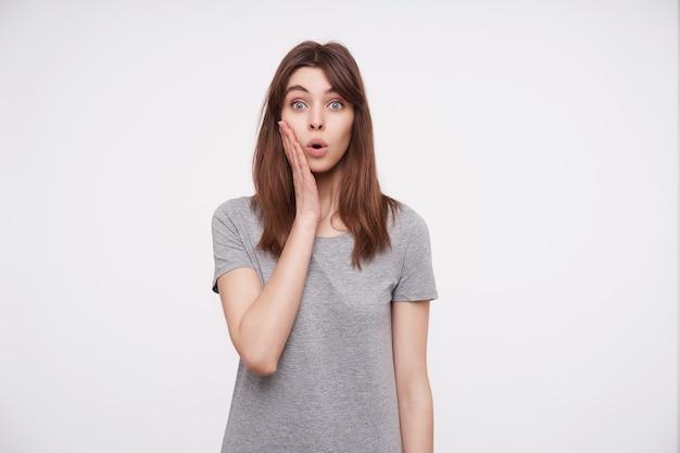 Erstaunte junge hübsche brünette frau mit lässiger frisur, die überraschend ihre blauen augen abrundet und erhobene handfläche auf ihrer wange hält, während sie auf weiß steht