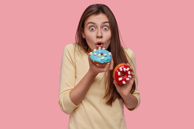 Erstaunte junge süße europäische frau birtes funkelte köstlichen donut, hält die augen weit offen, gekleidet in gelben pullover, hat leckeren snack