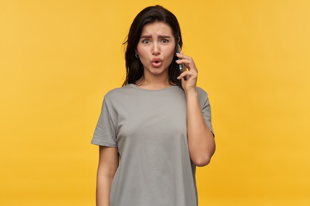 Erstaunte schockierte brünette junge frau im grauen t-shirt, die am handy über gelber wand spricht