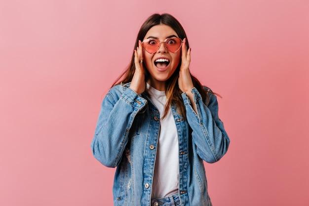 Erstaunte süße frau, die kamera mit offenem mund betrachtet. vorderansicht des überraschten mädchens in der jeansjacke lokalisiert auf rosa hintergrund.