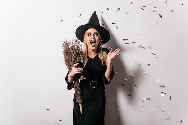 Erstaunte süße hexe im hut, die wein trinkt. debonair blonde dame im schwarzen kleid, das in halloween entspannt.