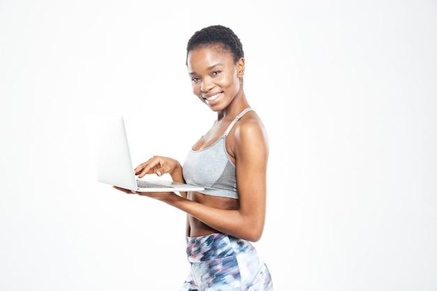 Erstaunte süße junge afroamerikanische sportlerin mit einem laptop
