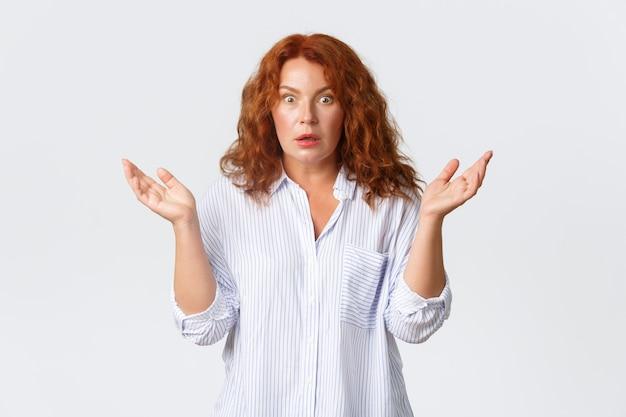 Erstaunte und besorgte rothaarige frau mittleren alters, mutter reagiert auf verwirrende seltsame nachrichten, hebt die hände zur seite und schnappt besorgt nach luft, stehende weiße wand.