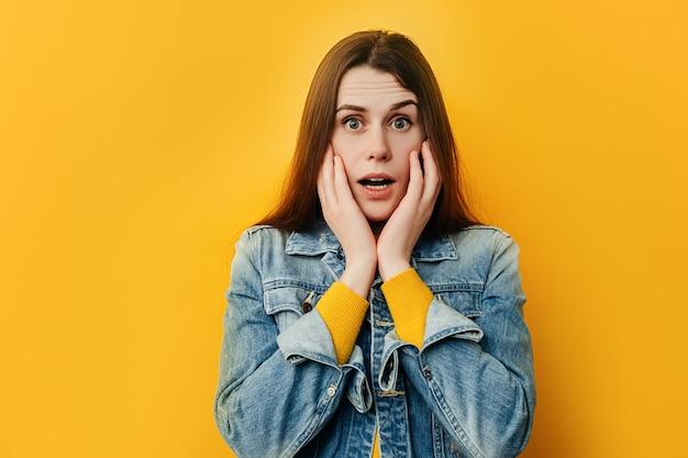 Erstaunte verängstigte junge frau packt gesicht, steht alarmiert als angst vor etwas, trägt eine jeansjacke, isoliert auf gelbem studiohintergrund
