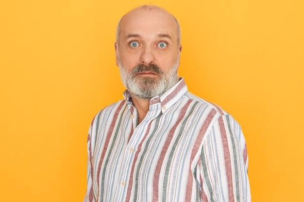Erstaunter älterer kahler unrasierter mann, der gestreiftes hemd öffnet, das weit aufgerissene augen öffnet, überrascht überrascht wird und plötzliche unerwartete nachrichten erhält, die isoliert vor gelbem studiowandhintergrund posieren