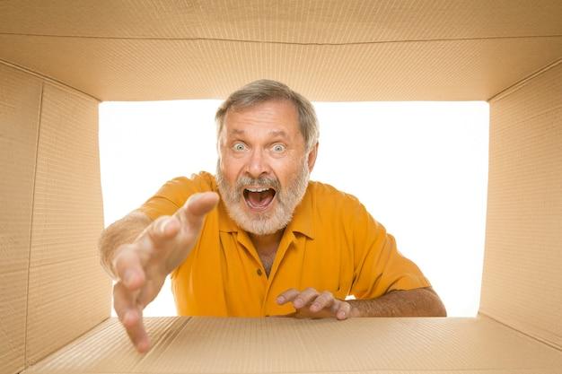 Erstaunter älterer mann, der das größte postpaket lokalisiert auf weiß öffnet. glückliches männliches model oben auf dem karton, der nach innen schaut.