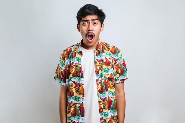 Erstaunter asiatischer junger mann mit offenem mund und hervortretenden augen, der die kamera isoliert auf weißem hintergrund betrachtet