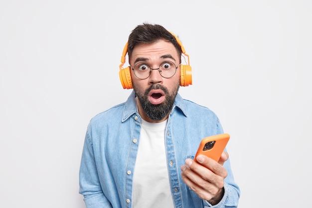 Erstaunter bärtiger erwachsener mann starrt verwanzte augen kann nicht glauben, dass etwas handy hält hört musik über kopfhörer trägt brille und hemd