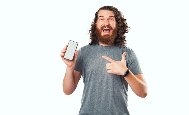 Erstaunter bärtiger hipster-mann, der auf smartphone-bildschirm über weißem hintergrund zeigt