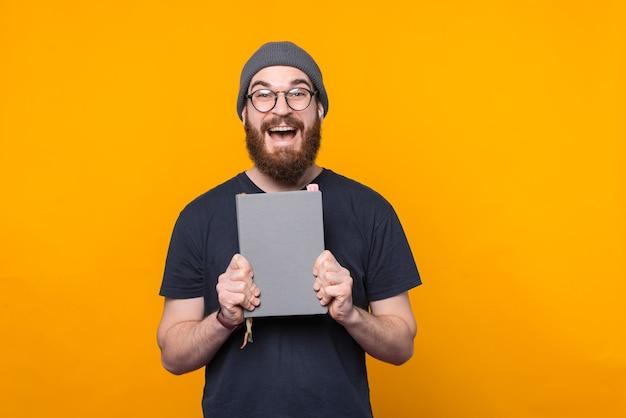 Erstaunter bärtiger hipster-mann, der perfekten planer für planungszeit hält