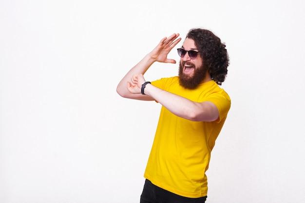 Erstaunter bärtiger mann, der auf smartwatch schaut und gestikuliert