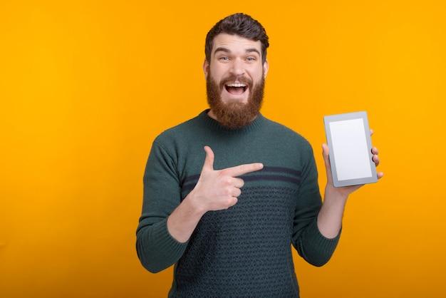 Erstaunter bärtiger mann, der auf tablettbildschirm zeigt