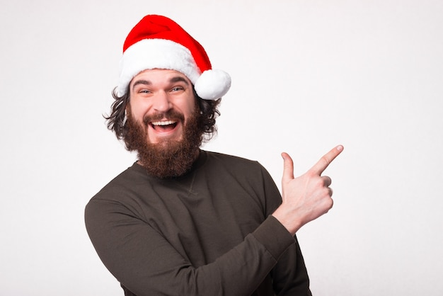 Erstaunter bärtiger mann, der weg zeigt, der weihnachtsmannhut trägt