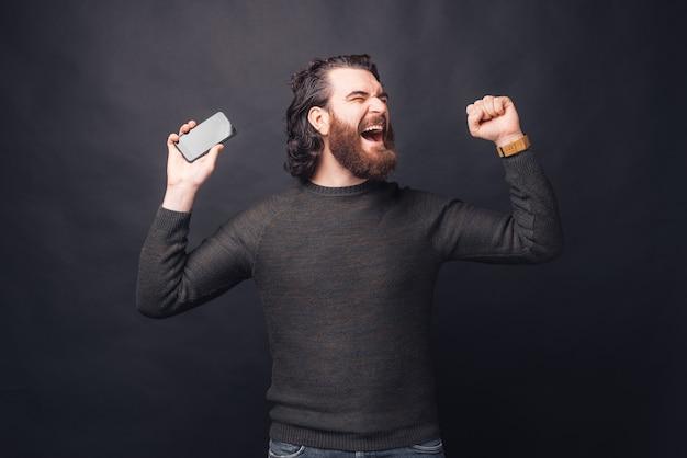 Erstaunter bärtiger mann in lässigem feiern des erfolgs und halten des smartphones