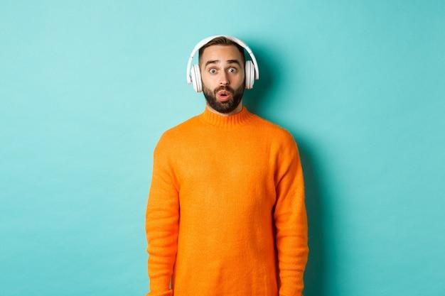 Erstaunter erwachsener mann, der musik in kopfhörern hört, kamera betrachtet mit ton beeindruckt, über türkisfarbenem hintergrund stehend.