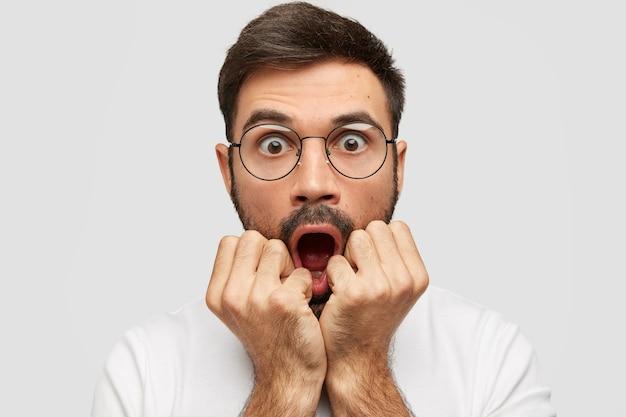 Erstaunter europäischer mann fühlt sich betäubt, lässt den kiefer fallen, hält die hände in der nähe des mundes, hat augen abgehört, hört schreckliche nachrichten vom gesprächspartner, steht an der weißen wand. menschen und negative emotionen konzept