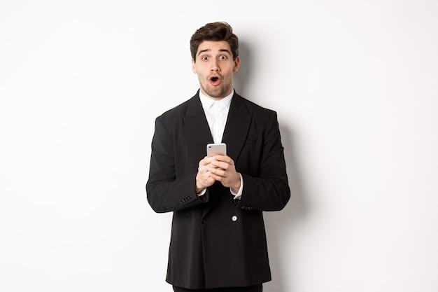 Erstaunter, gutaussehender kerl im schwarzen anzug, der auf ein cooles promo-angebot reagiert, das handy hält und vor weißem hintergrund steht