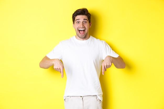 Erstaunter gutaussehender mann, der mit den fingern nach unten zeigt, ein banner mit aufregung zeigt und auf gelbem hintergrund steht