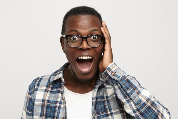 Erstaunter junger afroamerikaner-hipster, der brille und kariertes hemd über weißem t-shirt trägt