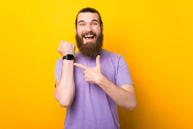Erstaunter junger bärtiger mann, der auf seine neue smartwatch über gelbem hintergrund zeigt
