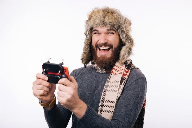 Erstaunter junger bärtiger mann im schal und in der wintermütze, die am smartphone mit joystick spielen