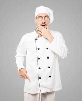 Erstaunter junger koch mit einer geste des schocks