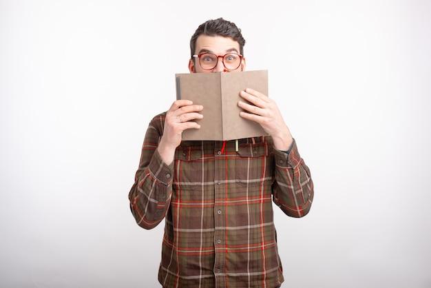 Erstaunter junger mann, der eine brille auf weißen stellen trägt, bedeckt sein gesicht mit einem geöffneten buch. lesezeit.