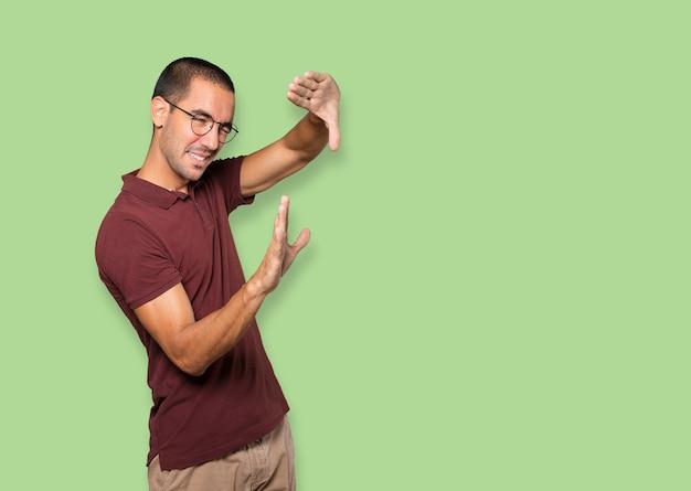 Erstaunter junger mann, der eine geste macht, ein foto mit den händen zu machen
