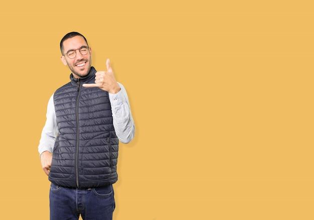 Erstaunter junger mann, der eine geste macht, mit der hand zu rufen