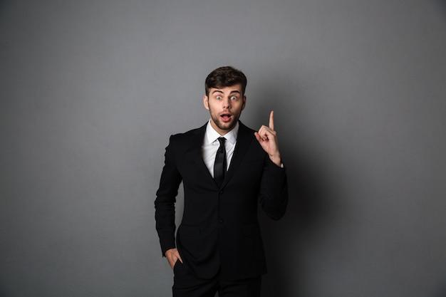 Erstaunter junger mann im anzug, der mit dem finger nach oben zeigt,