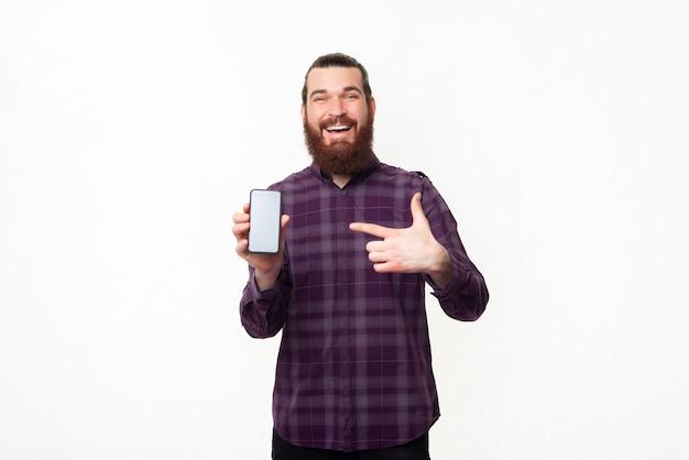 Erstaunter junger mann mit bart, der auf smartphone zeigt