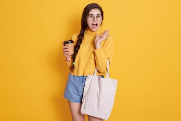 Erstaunter käufer mit langem zopf, der kaffee zum mitnehmen und einkaufstasche in händen hält