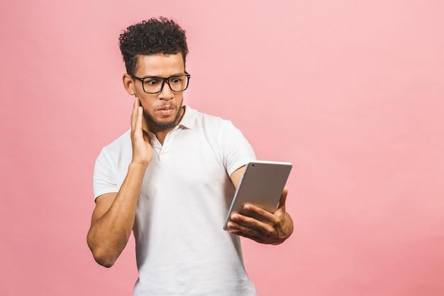 Erstaunter kerl mit digitalem tablet, der über social-media-nachrichten schockiert aussieht