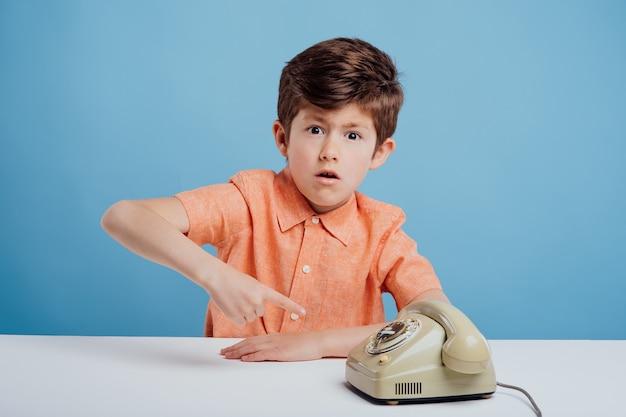 Erstaunter kinderjunge mit altem telefonblick auf die kamera, die auf das telefon zeigt, das am tisch sitzt blau ...