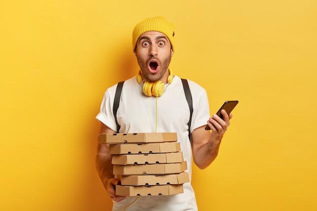 Erstaunter lieferbote erhält bestellungen von kunden per smartphone, hält stapel papppizzaschachteln, trägt rucksack, trägt hut und t-shirt, isoliert über gelbem hintergrund, arbeitet im restaurant