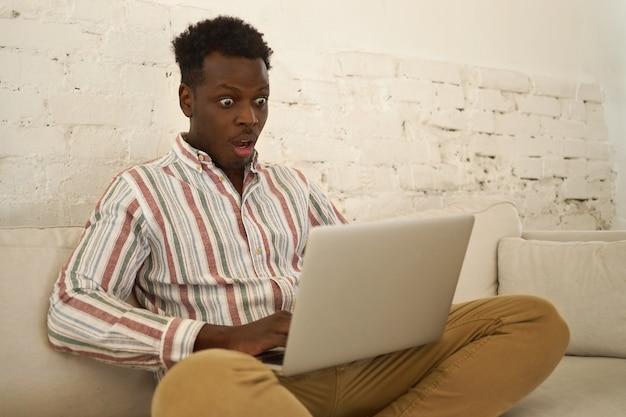 Erstaunter lustiger junger afroamerikaner, der auf dem sofa mit gefalteten beinen sitzt und den mund öffnet, während er unerwartete nachrichten liest